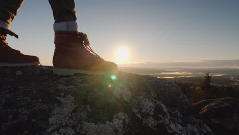 The-Traveler-s-Feet-At-The-Top-Of-The-Peak-Through-Them-Shines-The-Rising-Sun-And-Beautiful-Landscap