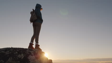 A-Successful-Active-Woman-Stands-On-Top-Of-A-Mountain-With-Endless-Horizons-In-Front-On-Top-Of-The-W