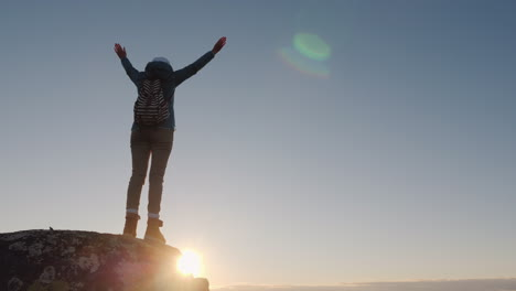 A-Successful-Woman-Traveler-At-The-Top-Of-The-Mountain-Raises-Her-Hands-Up-Reach-The-Top-Of-The-Conc