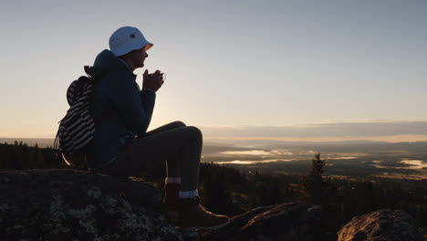 A-Traveler-Drinks-Tea-From-A-Mug-At-The-Peak-Of-The-Mountain-Sits-On-A-Rock-In-The-Background-A-Red-
