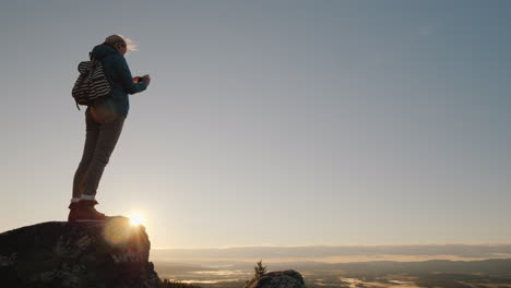 An-Active-Woman-Takes-Pictures-Of-A-Beautiful-Landscape-At-Her-Feet-Standing-On-Top-Of-A-Mountain-Tr