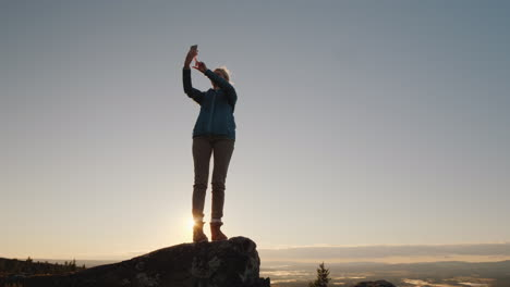 An-Active-Woman-Takes-Pictures-Of-Herself-On-The-Peak-Of-A-High-Mountain-At-Dawn-Stands-On-Top-Perso