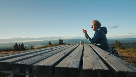 A-Woman-Sits-At-A-Table-Uses-Her-Phone-High-In-The-Mountains-Of-Norway-4k-Video