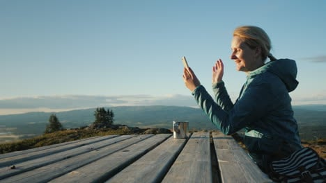 The-Traveler-Is-Talking-On-Video-Chat-Sits-At-A-Table-High-In-The-Mountains-Against-The-Backdrop-Of-