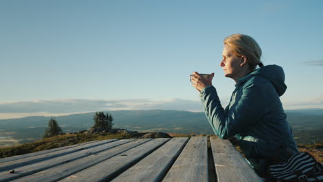 A-Woman-Traveler-Sits-At-A-Table-High-In-The-Mountains-Drinking-Tea-Far-From-Civilization-Nature-Of-
