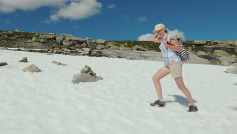 A-Woman-Is-Walking-On-The-Snow-In-The-Mountains-Outside-It-s-A-Hot-Summer-The-Snow-Has-Not-Melted-Ye