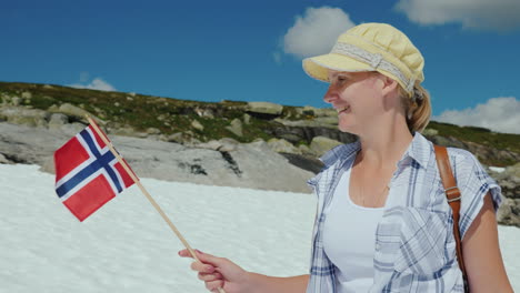 Woman-With-The-Flag-Of-Norway-On-A-Snowy-Peak-Summer-The-Snow-Has-Not-Melted-Yet-Tourism-And-Travel-