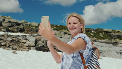 A-Happy-Woman-Doing-Selfie-On-A-Glacier-In-Norway-Hot-Weather-But-The-Snow-Has-Not-Melted-Yet-The-Am