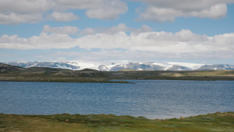 Go-Along-The-Beautiful-Landscape-Of-Norway-In-The-Distance-You-Can-See-Mountains-And-A-Glacier-On-To