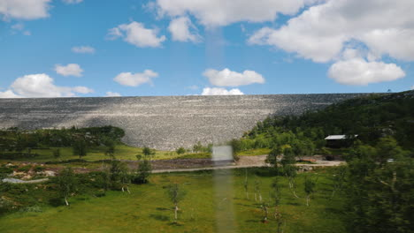 View-From-A-Car-Window-At-A-Landscape-In-Norway-With-A-Large-Stone-Dam