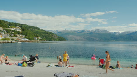 Tourists-Bathing-And-Resting-On-A-Small-Beach-Amidst-A-Picturesque-Fjord