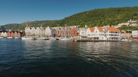 A-Street-Of-The-Famous-Colored-Wooden-Houses-In-Bergen-In-The-Foreground-A-Luxurious-Yacht