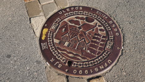 Metal-Sewer-Hatch-With-Images-Of-Houses-And-Sailboats-Original-Decoration-Of-The-City-In-Bergen