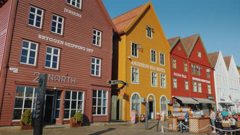A-Street-With-Famous-Wooden-Houses-In-Bergen-Next-To-Summer-Cafes-Where-Many-Tourists-Rest
