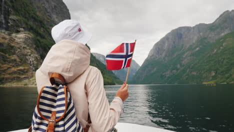 A-Tourist-With-A-Flag-Of-Norway-Stands-On-The-Nose-Of-A-Cruise-Ship-Journey-Through-The-Picturesque-