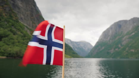 The-Norwegian-Flag-Flies-In-The-Wind-Against-The-Backdrop-Of-A-Majestic-Fjord-Cruise-On-The-Fjords-O