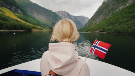 A-Person-With-A-Norwegian-Flag-In-His-Hand-Travels-On-A-Ship-On-A-Picturesque-Fjord