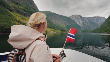 Active-Woman-With-The-Flag-Of-Norway-On-The-Bow-Of-The-Ship-Fjord-Cruises-Trip-To-Scandinavia-4k-Vid