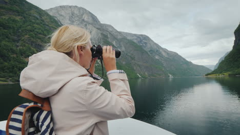 A-Woman-Is-Standing-On-The-Bow-Of-The-Ship-Looking-Through-Binoculars-Cruise-On-The-Fjords-Of-Norway