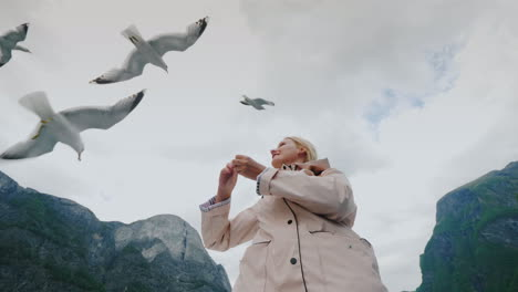 A-Woman-Is-Feeding-A-Gull-That-Flies-By-Trust-And-Tame-The-Concept-Journey-Through-The-Fjords-Of-Nor
