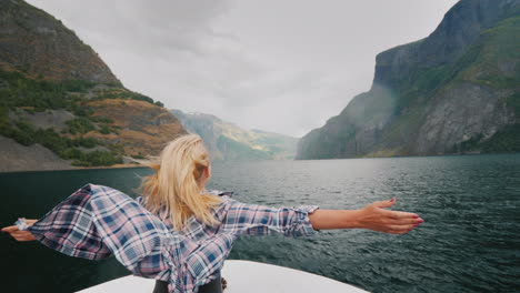 A-Free-Woman-Stands-With-Her-Hands-To-The-Sides-On-The-Bow-Of-A-Cruise-Ship-Traveling-The-Fjords-Of-