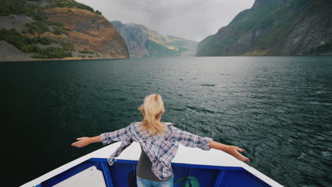 A-Woman-Is-Standing-On-The-Bow-Of-The-Ship-Sailing-Over-The-Fjord-In-Norway-Enjoys-The-Journey-The-W