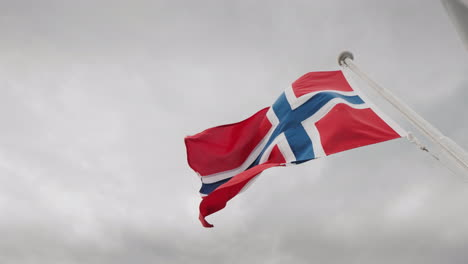 Flag-Of-Norway-Fluttering-Over-A-Stormy-Sky-Cruise-On-The-Fjords-Of-Norwayy-4k-Video