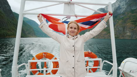 A-Young-Woman-With-The-Flag-Of-Norway-Stands-At-The-Stern-Of-A-Pleasure-Boat-A-Cruise-On-A-Picturesq