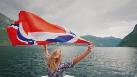 An-Active-Woman-With-A-Large-Norwegian-Flag-Is-Standing-On-The-Bow-Of-A-Cruise-Ship-Fjord-Cruise-In