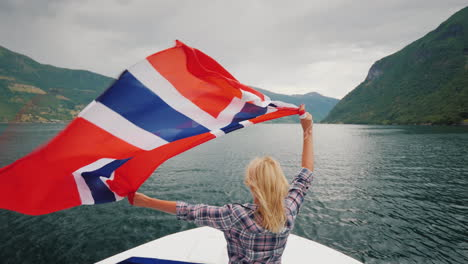 An-Active-Woman-With-A-Large-Norwegian-Flag-Is-Standing-On-The-Bow-Of-A-Cruise-Ship-Fjord-Cruise-In-