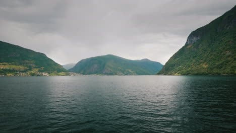 View-From-The-First-Person-Sailing-Along-The-Beautiful-Fjords-In-Norway-High-Cliffs-Off-The-Coast-An