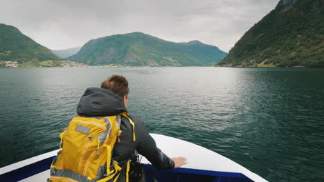 A-Man-With-A-Backpack-Travels-Through-A-Picturesque-Fjord-In-Norway-Standing-On-The-Bow-Of-The-Ship-