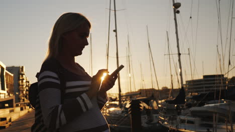Silhouette-Of-A-Woman-Using-A-Smartphone-Near-The-Pier-Where-Many-Yachts-Are-Moored