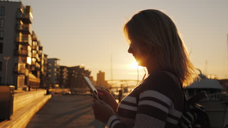A-Woman-In-Headphones-Uses-A-Smartphone-On-The-Pier-On-The-Background-Of-Private-Yachts-At-Sunset-Th