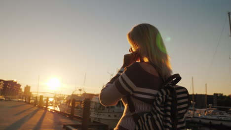 A-Woman-Is-Walking-Along-The-Pier-At-Sunset-Listening-To-Music-On-Headphones-The-City-Of-Bergen-In-N