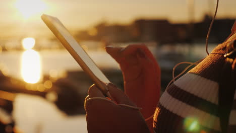Hands-Of-A-Woman-With-A-Smartphone-On-The-Background-Of-A-Pier-With-Yachts-At-Sunset-4k-Video