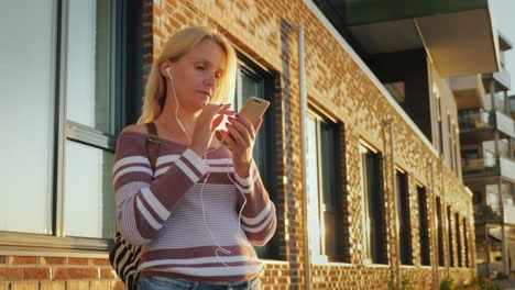 A-Young-Woman-Is-Using-The-Application-On-A-Smartphone-Standing-By-A-Beautiful-Brick-Building-At-Sun
