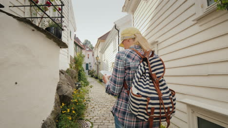 Tourist-With-A-Map-In-Her-Hands-Walking-Through-The-Narrow-Streets-Of-Bergen-In-Norway-Holidays-In-S