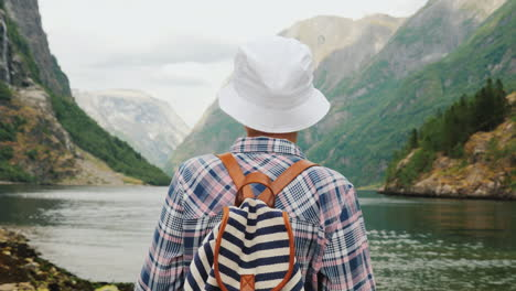 A-Woman-With-A-Backpack-Behind-Her-Back-Looks-At-The-Majestic-Fjord-In-Norway-Travel-And-Tourism-In-