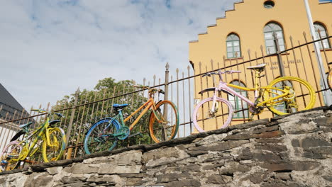 Several-Colorful-Bicycles-Stand-At-The-Fence-Original-Decoration-In-The-City
