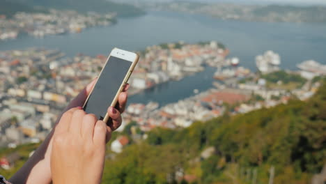 Female-Hands-With-A-Smartphone-Use-The-Phone-Against-The-Background-Of-The-City-Of-Bergen-4k-Video