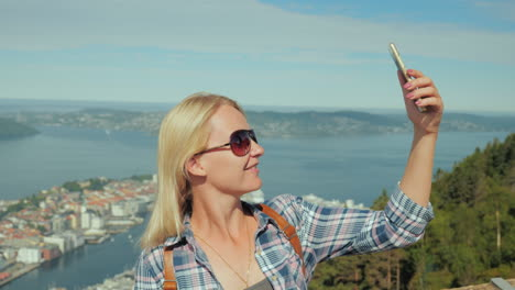 Woman-Tourist-Taking-Pictures-Of-Herself-Against-The-Background-Of-The-City-Of-Bergen-In-Norway-Tour