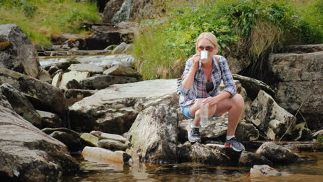 A-Woman-Drinks-Clean-Water-Recruited-From-A-Stream-Norway-Waterfall-Tvindefossen-4k-Video