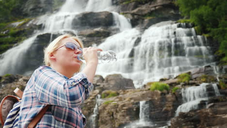 Young-Woman-Drinks-Water-On-The-Background-Of-The-Twin-Waterfall-Tvindefossen-In-Norway-Clean-Drinki