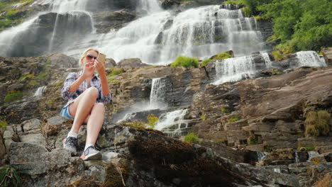 A-Traveler-Uses-A-Smartphone-Against-The-Background-Of-A-Waterfall-Tvindefossen-In-Norway-4k-Video