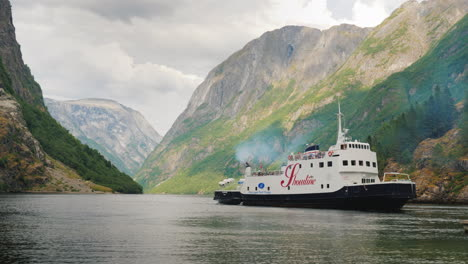 Cruise-Ship-With-Tourists-Approaches-The-Shore-Against-The-Backdrop-Of-The-Picturesque-Fjord-In-Norw