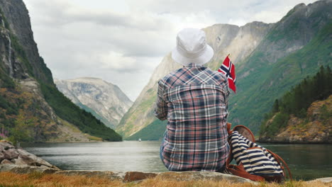 Tourist-With-Backpack-And-Flag-Of-Norway-Admires-Grandiose-Fjord-Tourism-In-Scandinavia-Concept-4k-V