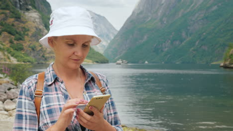 A-Woman-Uses-A-Smartphone-On-The-Shore-Of-A-Picturesque-Fjord-In-Norway-Always-In-Touch-Technology-O