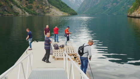 A-Group-Of-Tourists-Are-Fishing-On-A-Pier-In-The-Background-Of-A-Picturesque-Fjord-In-Norway