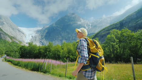 A-Woman-Walks-Along-The-Path-To-The-Briksdal-Glacier-In-Norway-A-Rear-View-Traveling-In-Scandinavia
